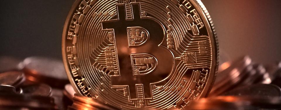 złota moneta z wybitym logiem bitcoina