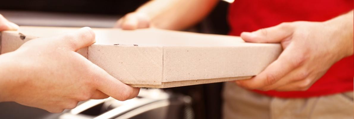 dostawca pizzy przekazujący karton z pizzą drugiej osobie