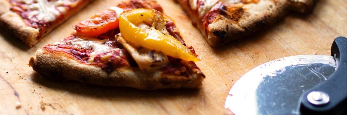 kawałki pizzy na drewnianym blacie z położonym obok okrągłym nożem do pizzy